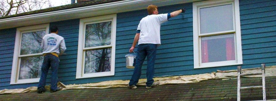 men painting a house blue